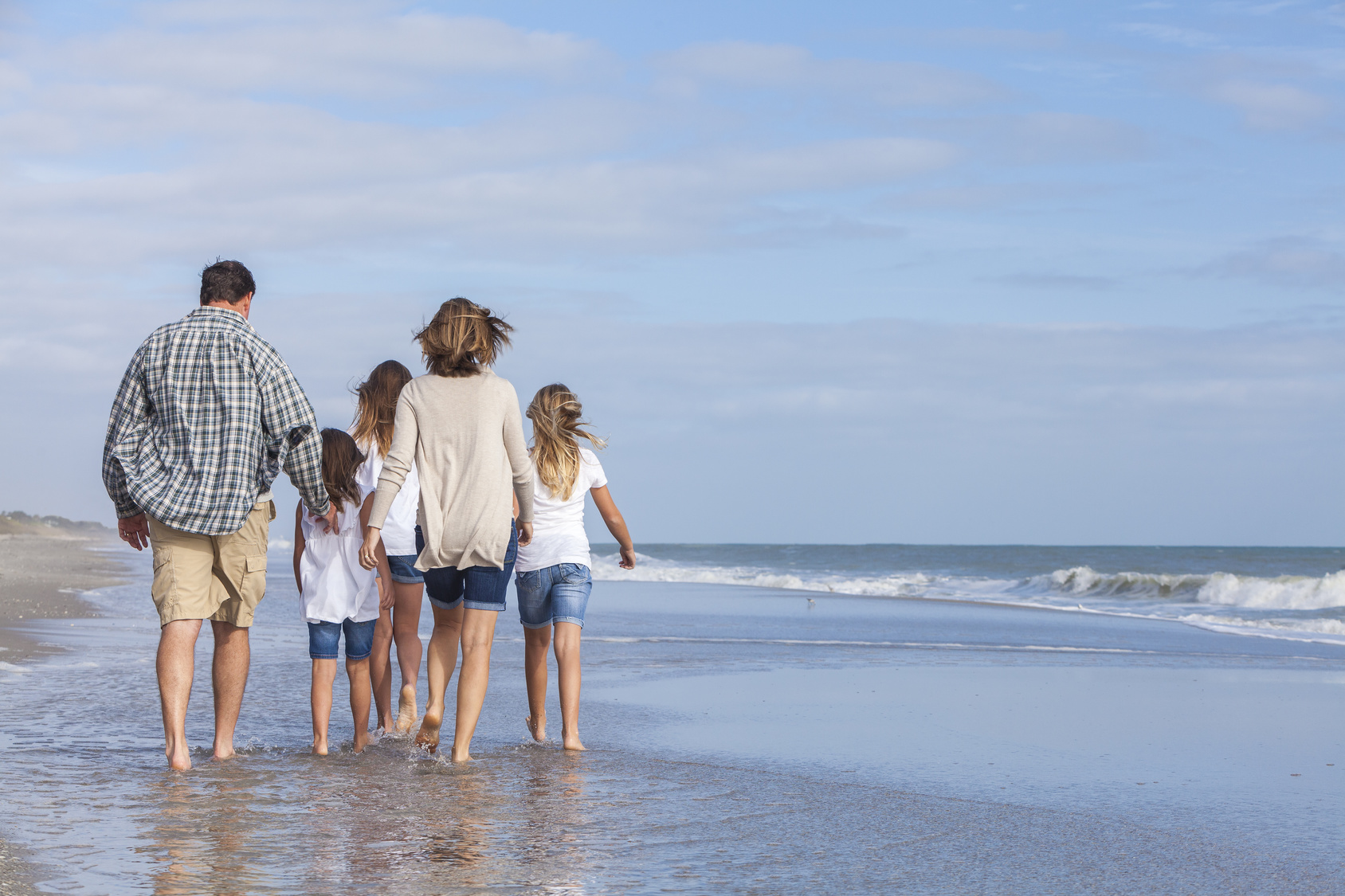 A family strolling on the beach contemplating a 1035 exchange life insurance review.